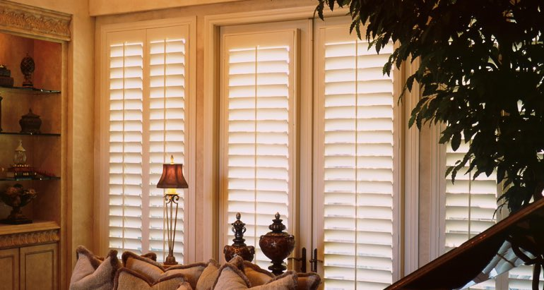 Plantation shutters on french door and window in Denver parlor