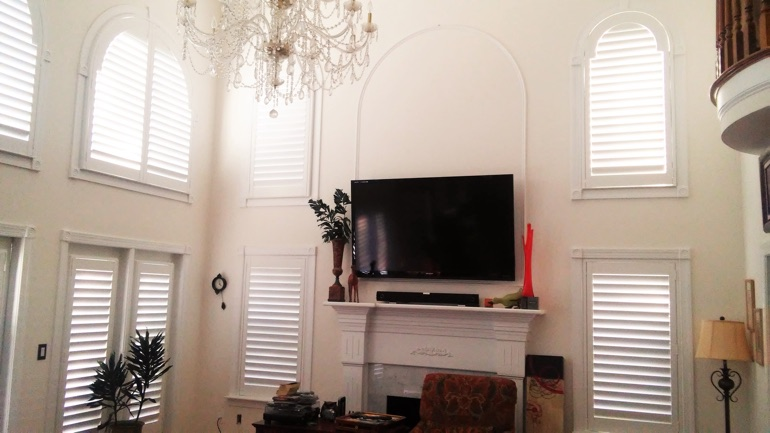 Denver great room with mounted TV and arched windows.