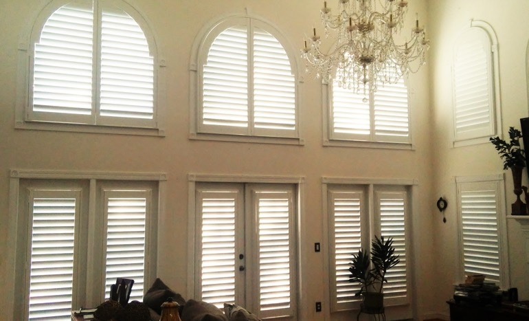 Family room in two-story Denver home with plantation shutters on high windows.