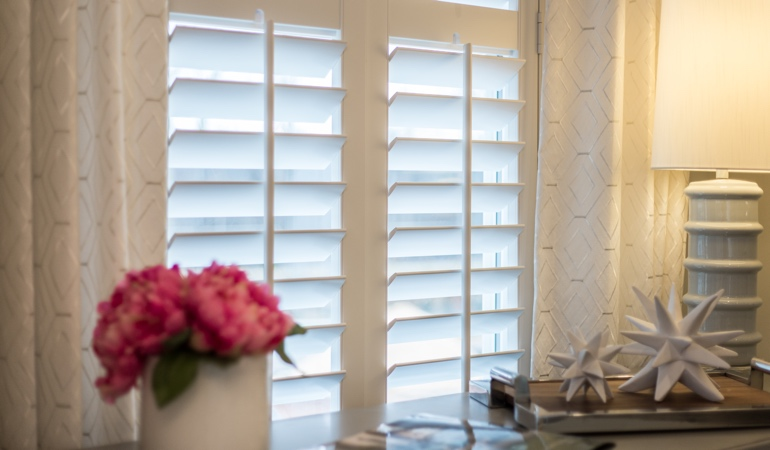 Plantation shutters by flowers in Denver