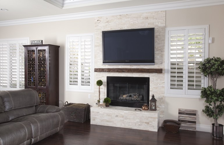 White plantation shutters in a Colorado Springs living room with plank hardwood floors.