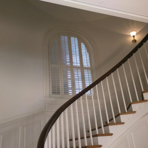White plantation shutters covering rounded window located in round stairwell.
