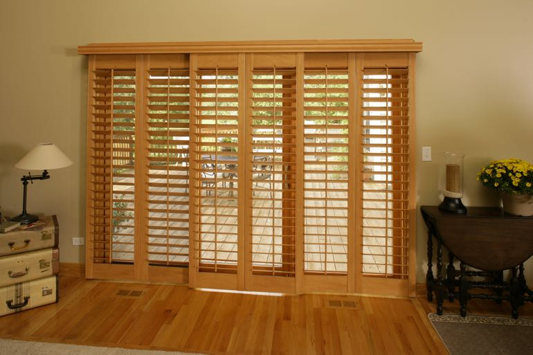 plantation shutters on sliding door going to outdoor porch.