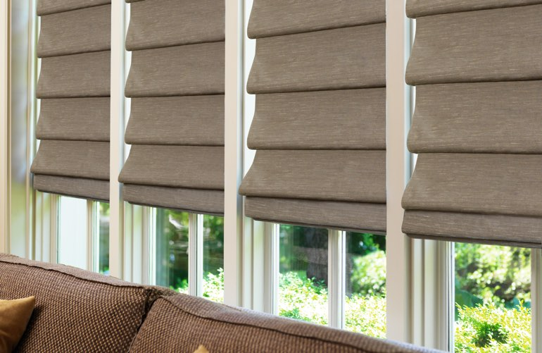Sunroom window with brown Roman shades