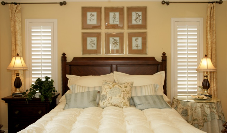 Tall plantation shutters framing bed in a bedroom in Colorado Springs