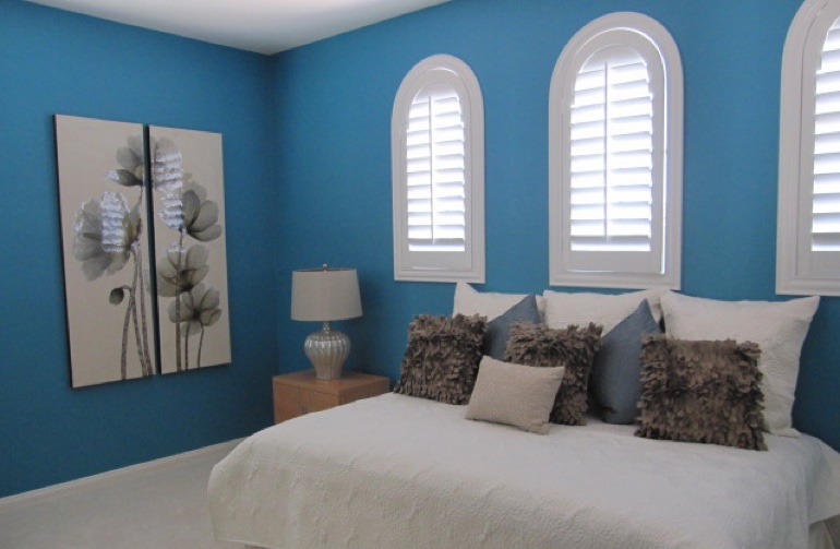 Bedroom with blue paint and white plantation shutters